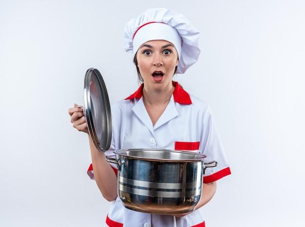 Jovem cozinheira assustada vestindo uniforme de chef segurando uma panela com tampa isolada no fundo branco