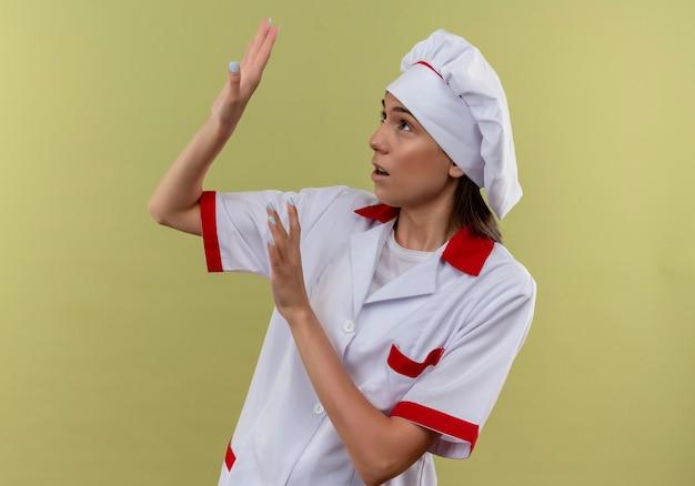 Jovem cozinheira caucasiana assustada com uniforme de chef finge se defender com as mãos olhando para o lado no verde com espaço de cópia