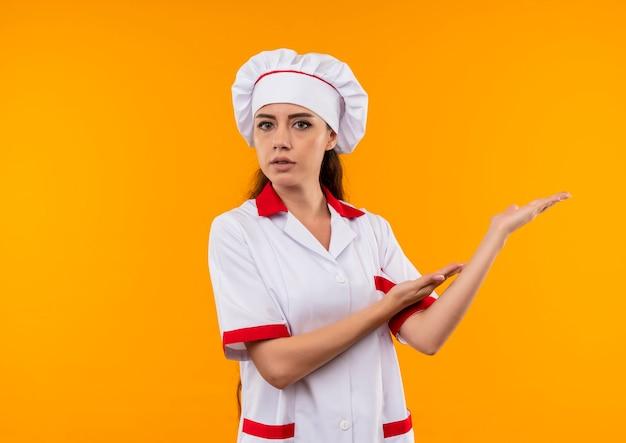 Jovem cozinheira caucasiana confiante com uniforme de chef aponta para o lado com as duas mãos isoladas na parede laranja com espaço de cópia