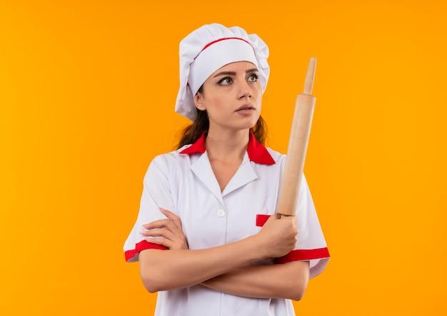 Jovem cozinheira caucasiana confiante com uniforme de chef cruza os braços e segura o rolo de massa isolado em um fundo laranja com espaço de cópia