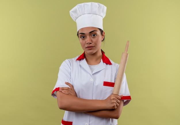 Jovem cozinheira caucasiana confiante com uniforme de chef cruza os braços e segura o rolo de massa isolado em um fundo verde com espaço de cópia