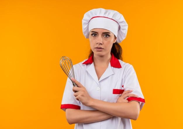 Jovem cozinheira caucasiana confiante com uniforme de chef cruza os braços e segura um batedor isolado em um fundo laranja com espaço de cópia