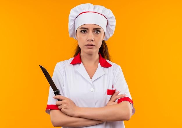 Jovem cozinheira caucasiana confiante com uniforme de chef cruza os braços e segura uma faca isolada em um fundo laranja com espaço de cópia