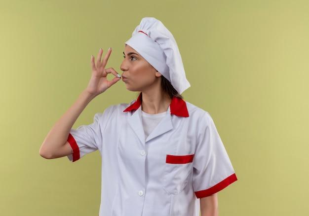Jovem cozinheira caucasiana confiante com uniforme de chef fazendo gestos deliciosos no verde com espaço de cópia