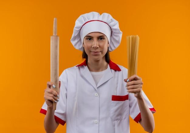 Jovem cozinheira caucasiana confiante com uniforme de chef segurando o rolo e um monte de espaguete isolado no espaço laranja com espaço de cópia