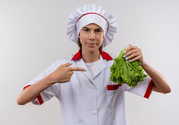 Jovem cozinheira caucasiana confiante em uniforme de chef segura e aponta para salada em branco com espaço de cópia