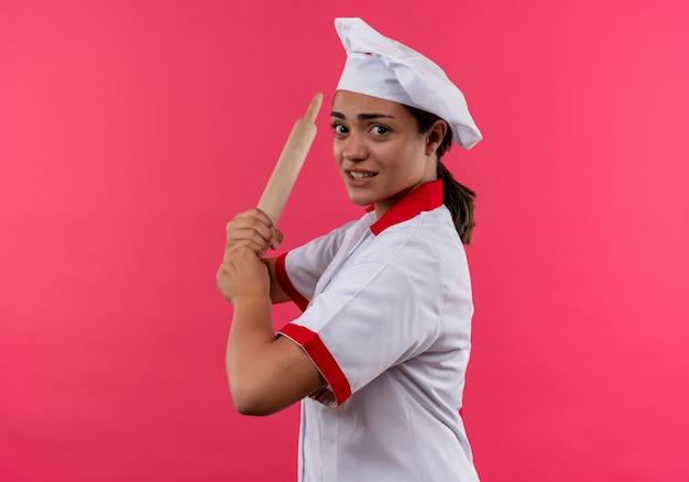 Jovem cozinheira caucasiana irritada com uniforme de chef fica de lado e segura o rolo de massa isolado no fundo rosa com espaço de cópia