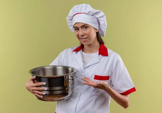 Jovem cozinheira caucasiana irritada com uniforme de chef segura e aponta para uma panela isolada em um fundo verde com espaço de cópia
