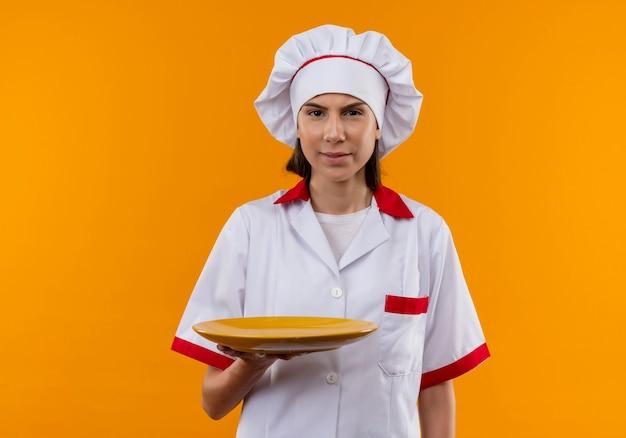 Jovem cozinheira caucasiana irritada com uniforme de chef segura o prato e olha para a câmera isolada em um fundo laranja com espaço de cópia