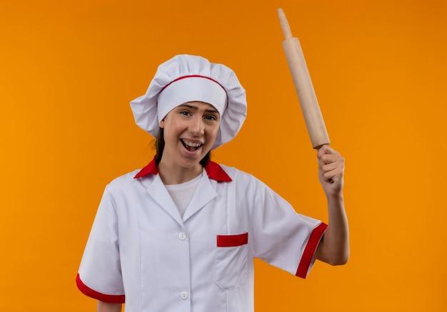 Jovem cozinheira caucasiana irritada com uniforme de chef segura o rolo de massa e olha para a câmera em laranja com espaço de cópia