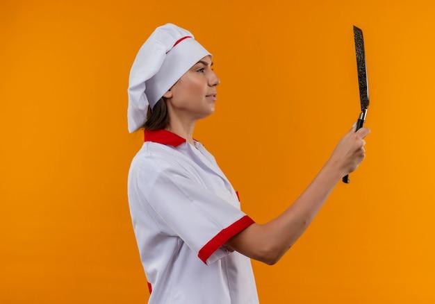 Jovem cozinheira caucasiana satisfeita com uniforme de chef, parada de lado, segurando e olhando para a frigideira