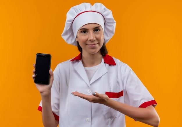 Jovem cozinheira caucasiana satisfeita com uniforme de chef segura e aponta para o telefone isolado no espaço laranja com espaço de cópia
