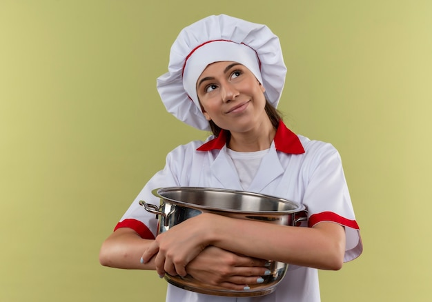 Jovem cozinheira caucasiana satisfeita com uniforme de chef segurando a panela com os braços e olhando para o lado verde com espaço de cópia