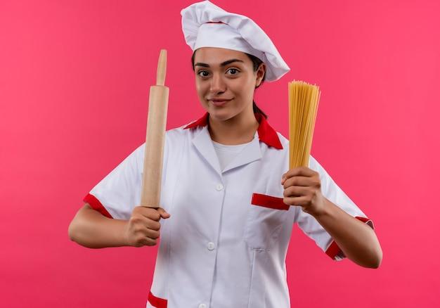 Jovem cozinheira caucasiana satisfeita com uniforme de chef segurando o rolo e um monte de espaguete isolado na parede rosa com espaço de cópia