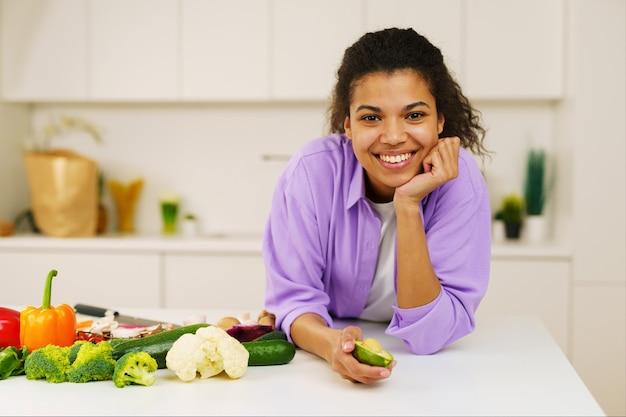 Jovem cozinheira com avental a preparar legumes na cozinha
