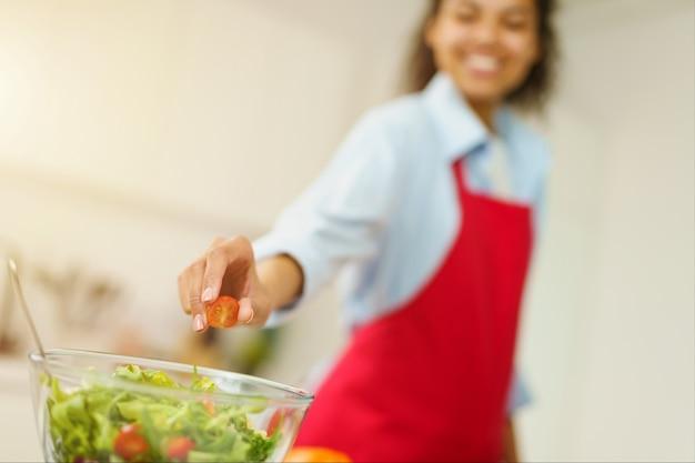 Jovem cozinheira com avental a preparar uma salada na cozinha