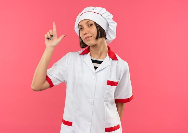 Jovem cozinheira confiante em uniforme de chef fazendo gesto de pistola isolado na rosa com espaço de cópia