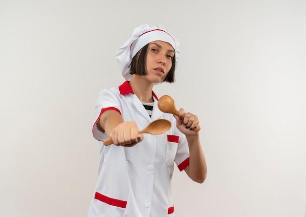 Jovem cozinheira confiante em uniforme de chef segurando e esticando colheres isoladas em branco com espaço de cópia