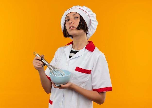Jovem cozinheira confiante em uniforme de chef segurando um batedor e uma tigela isolada em laranja com espaço de cópia