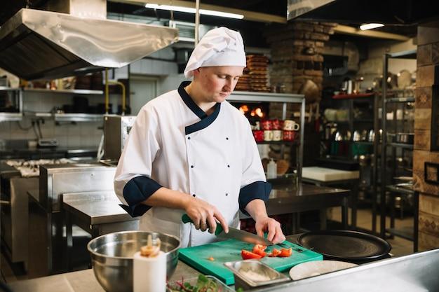 Jovem cozinheira cortando tomate a bordo