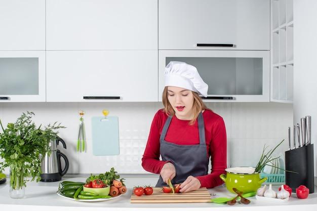 Jovem cozinheira de avental cortando tomates