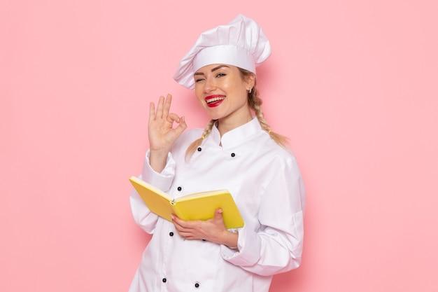 Jovem cozinheira de terno branco lendo um caderno amarelo com um sorriso no cozinheiro do espaço rosa