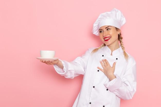 Jovem cozinheira de terno branco segurando uma xícara de café com um leve sorriso na cozinha do espaço rosa