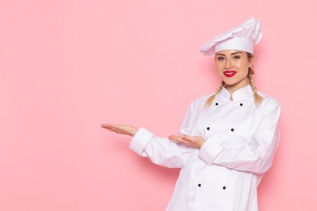 Jovem cozinheira em terno branco de cozinheira de frente, sorrindo levemente e posando na cozinha rosa