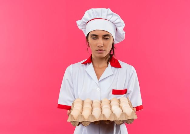 Jovem cozinheira entediada usando uniforme de chef segurando lote de ovos na parede rosa isolada com espaço de cópia