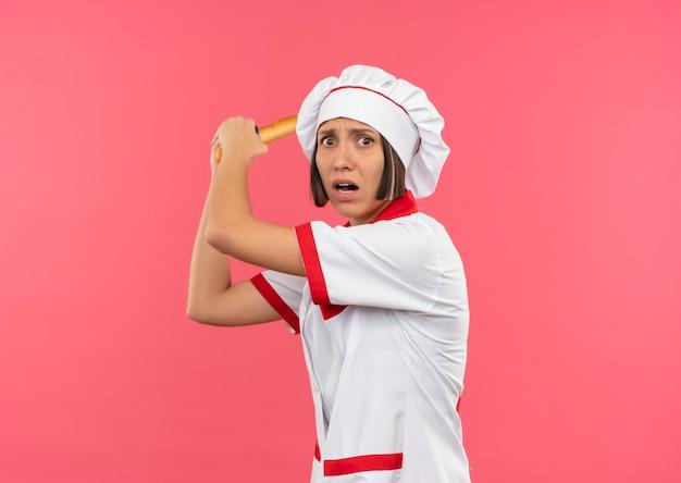 Jovem cozinheira furiosa com uniforme de chef segurando um palito e se preparando para bater em alguém isolado no rosa