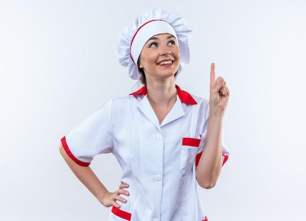 Jovem cozinheira impressionada usando uniforme de chef aponta para cima colocando a mão no quadril isolado na parede branca