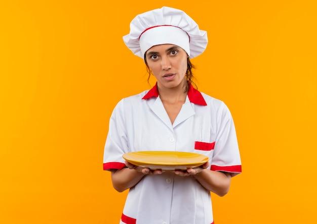 Jovem cozinheira impressionada usando uniforme de chef, segurando o prato na parede amarela isolada com espaço de cópia