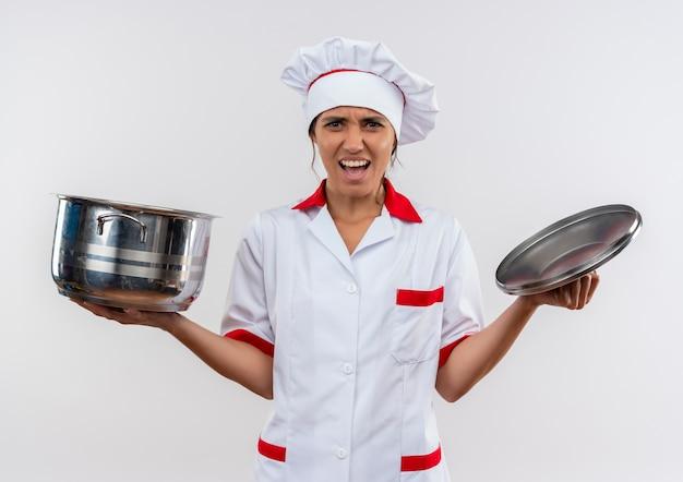 Jovem cozinheira preocupada vestindo uniforme de chef, segurando uma panela e a tampa na parede branca isolada