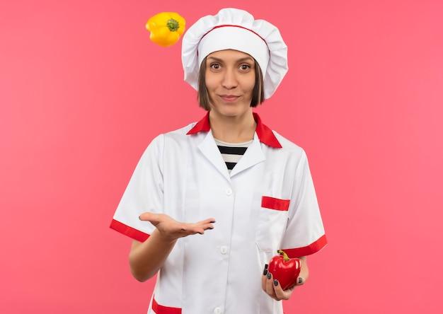 Jovem cozinheira satisfeita em uniforme de chef segurando e jogando pimentas isoladas em um fundo rosa com espaço de cópia