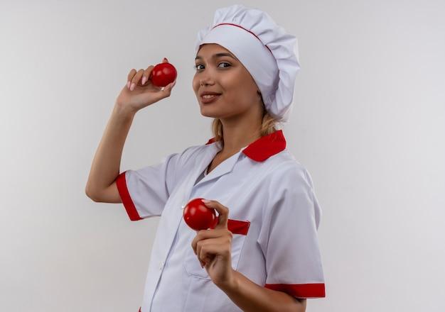 Jovem cozinheira satisfeita usando uniforme de chef segurando tomates na parede branca isolada