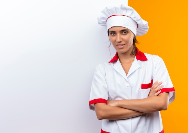 Jovem cozinheira satisfeita vestindo uniforme de chef em pé com parede branca e cruzando as mãos com espaço de cópia