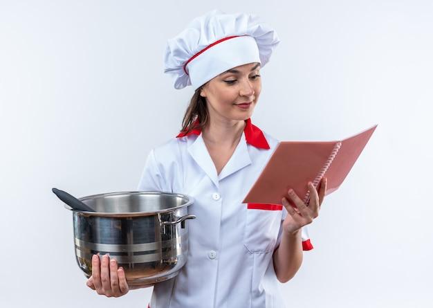 Jovem cozinheira satisfeita vestindo uniforme de chef, segurando uma panela e olhando para o caderno na mão, isolado no fundo branco