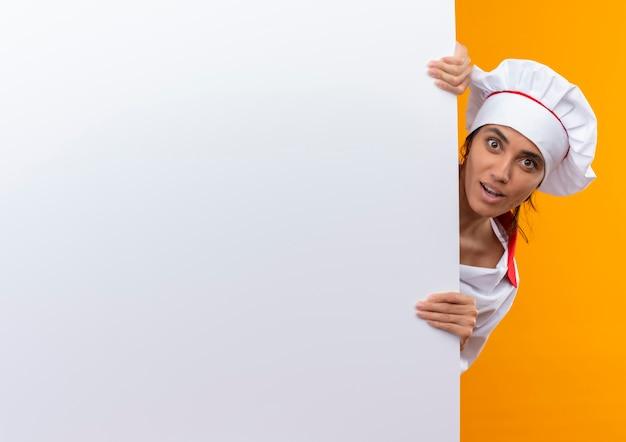 Jovem cozinheira surpresa, vestindo uniforme de chef, segurando uma parede branca com espaço de cópia