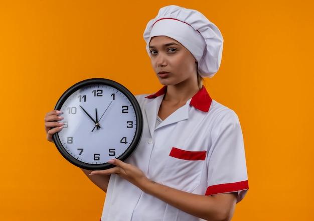 Jovem cozinheira usando uniforme de chef segurando um relógio de parede na parede laranja isolada