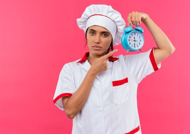 Jovem cozinheira vestindo uniforme de chef segurando e aponta para o despertador na parede rosa isolada com espaço de cópia