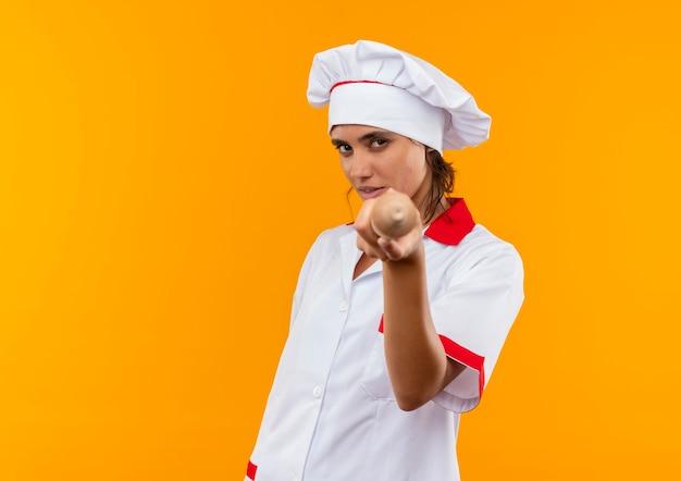 Jovem cozinheira vestindo uniforme de chef segurando o rolo para a câmera na parede amarela isolada com espaço de cópia