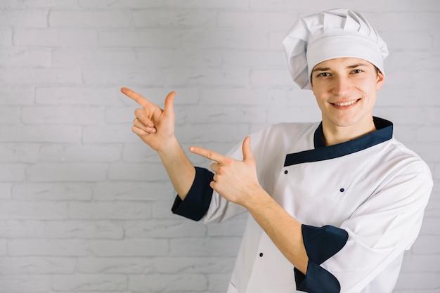 Jovem cozinheiro apontando os dedos em algum lugar