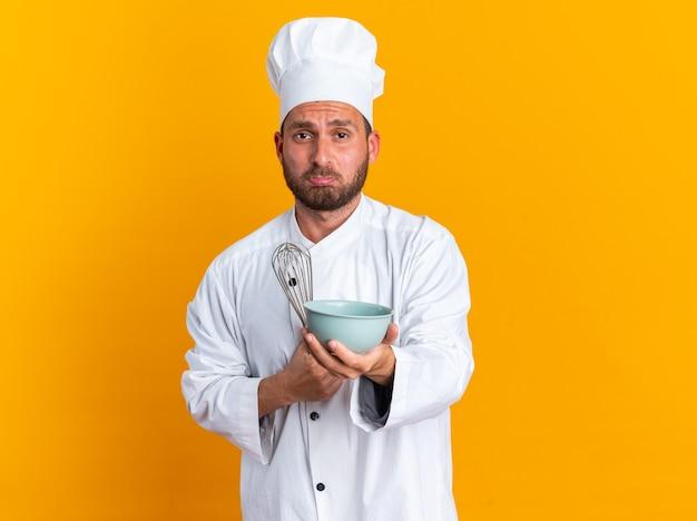 Jovem cozinheiro caucasiano com uniforme de chef e boné segurando um batedor, estendendo a tigela com os lábios contraídos