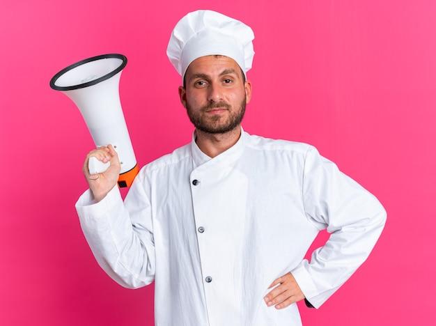 Jovem cozinheiro caucasiano confiante em uniforme de chef e boné segurando o alto-falante, segurando a mão na cintura, olhando para a câmera isolada na parede rosa