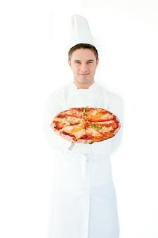 Jovem cozinheiro cheiro cheiro de pizza com olhos fechados