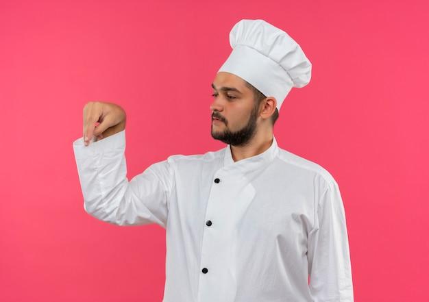 Jovem cozinheiro com uniforme de chef, adicionando sal e olhando para o lado isolado no espaço rosa