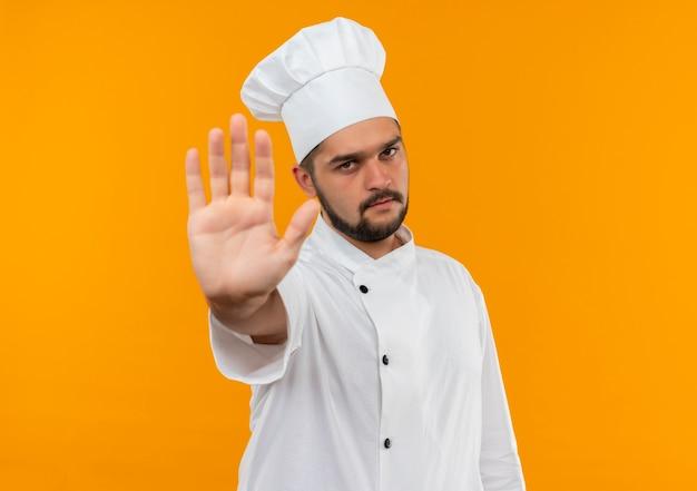 Jovem cozinheiro com uniforme de chef gesticulando para parar isolado no espaço laranja