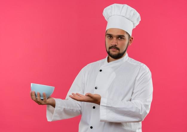 Jovem cozinheiro com uniforme de chef segurando a tigela isolada no espaço rosa