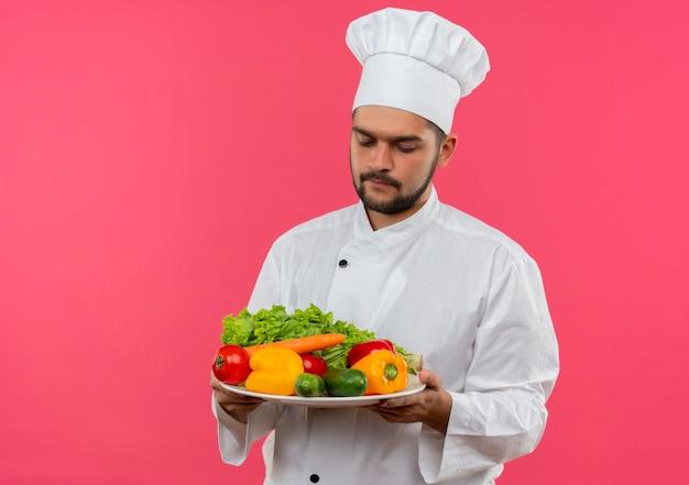 Jovem cozinheiro com uniforme de chef segurando e olhando para o prato de vegetais isolado no espaço rosa