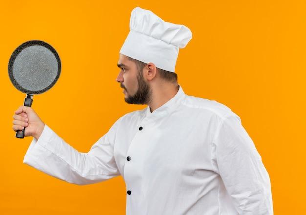 Jovem cozinheiro com uniforme de chef segurando e olhando para uma frigideira isolada em um espaço laranja